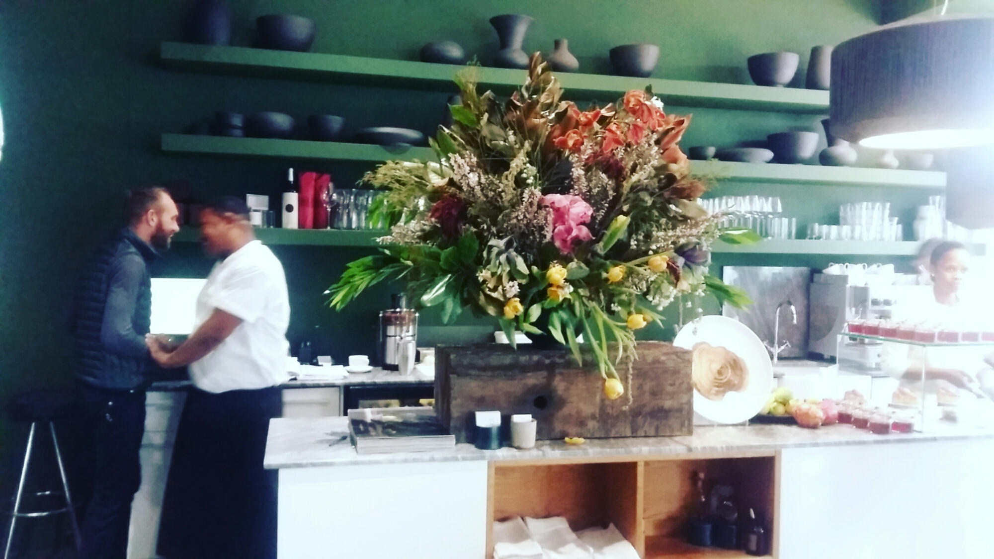 Exuberant floral display, tarts, fruit preserves and jellies on the service counter